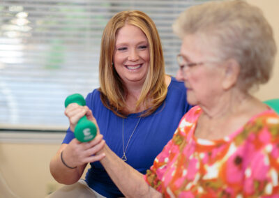 Female therapist helping a female elderly with arm exercises