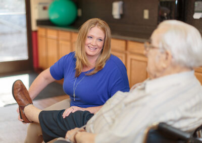 Female therapist stretching an elderly's leg