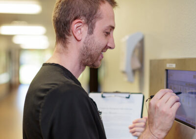 Male therapist interacting with a tablet attached to a wall