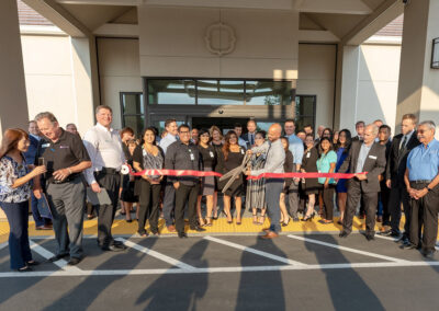Staff of Trellis Chino cutting red ribbon for grand opening