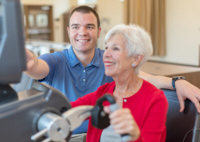 Therapist helping an elderly with exercise machine