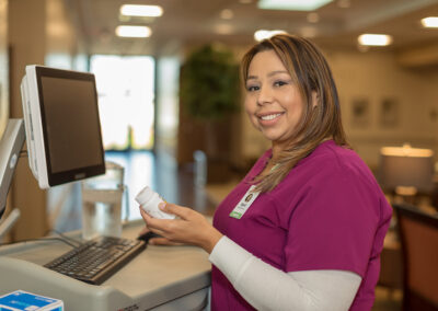 Nurse smiling and holding a bottle of medicine in front of computer