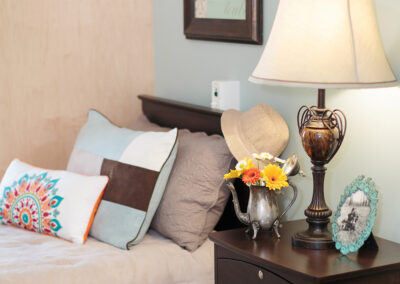 Picture of a private room with a hat hanging on the bed's headboard, vase of flowers, and a picture frame