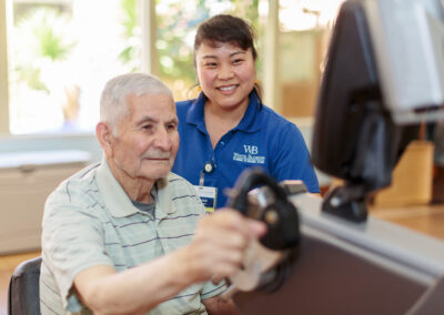 Therapist helping male elderly with exercise machine