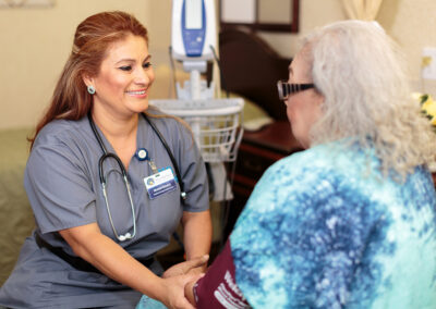 Nurse smiling and holding patient's hand