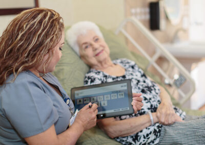 Nurse with iPad and elderly woman on bed