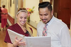 nurse and man smiling while looking at paperwork