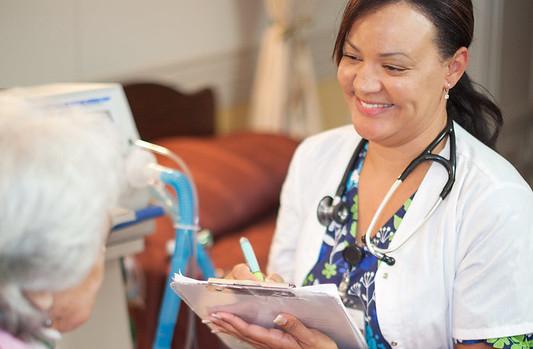 Caregiver at nurse's cart in hallway