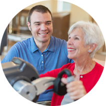 A senior smiling while performing rehabilitation exercises with a young man beside her.
