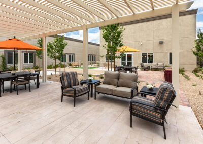 Outside seating under a large pergola for shade.