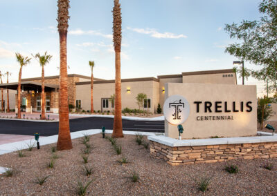 Trellis Centennial sign in front of the building with palm trees and desert landscaping out front.