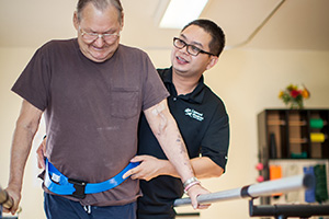 Physical therapist helping a patient walk during rehabilitation