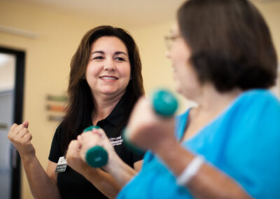 Rehab therapist working with a resident in the gym