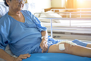 elderly woman with a knee wound and white bandage