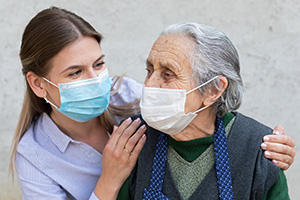 Nurse with elderly woman both wearing masks